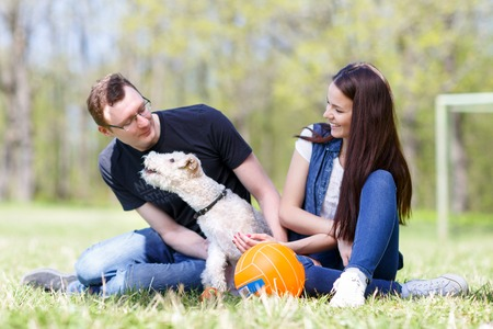 Happy young couple and their dog at the park Stock Photo