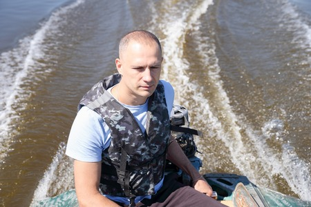 fatigues: man in army fatigues moved by motor boat Stock Photo