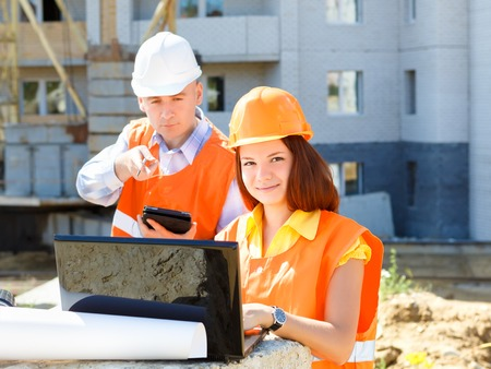 Portrait Of Male Architect And  Woman Discussing Plan at Construction Site photo