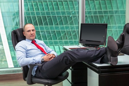 office shoes: businessman relaxing at the office with his shoes on the desk Stock Photo