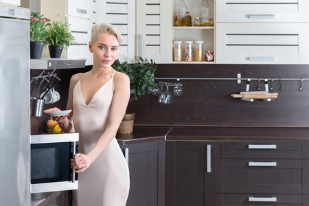 blondie: Blond woman cooking with a microwave in modern kitchen