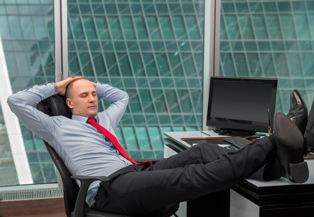 office shoes: businessman relaxing at the office with his shoes on the desk inside office building