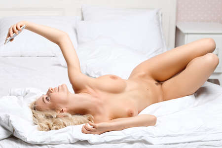 Beautiful naked girl making self on the bed at home