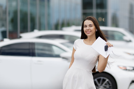 customer service representative: Smilling woman with keys and agreement on background of car dealership