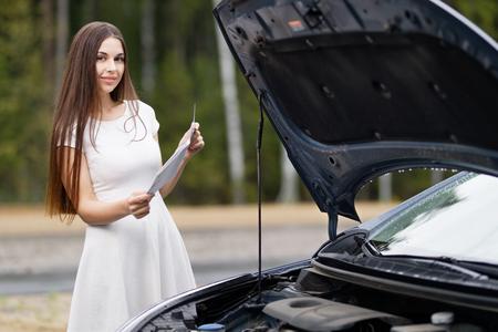 attractive woman in front of her car broken car