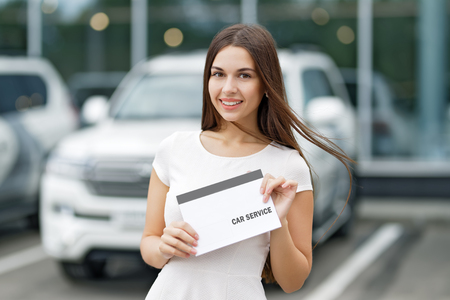 selling service: Smilling woman with agreement car service on background of dealership
