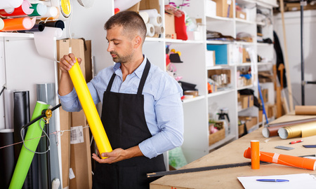 man designer and print operator with vinyl paper at the print manufacturing Stock Photo