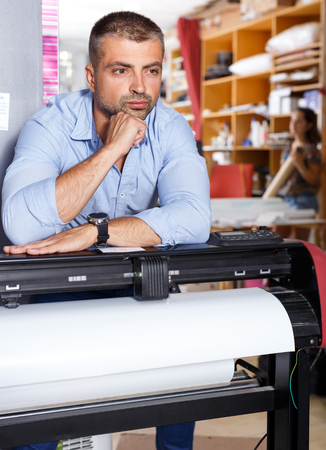 thoughtful man worker paper print work place Stock Photo