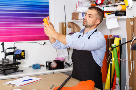 male design worker looks at colored paper Stock Photo