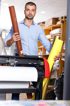 Man printing worker with rolls of colored paper Stock Photo