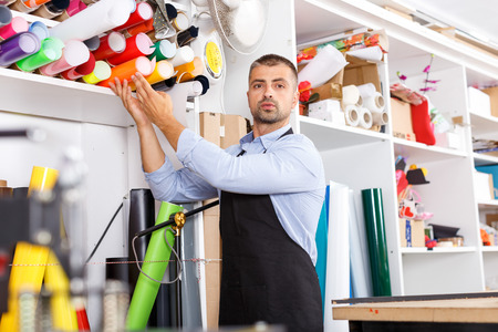 man designer and print operator with vinyl paper at the print manufacturing
