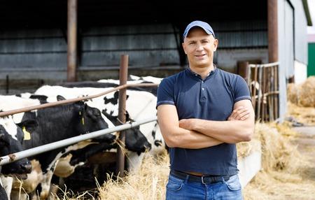 positive farmer with cows at farm