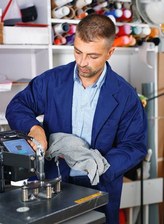 man worker makes print on shirt