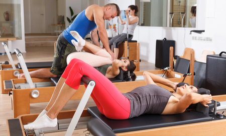 people in the gym doing exercises with modern fitness equipment