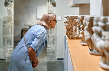 woman in historical museum looking at art object Stock Photo