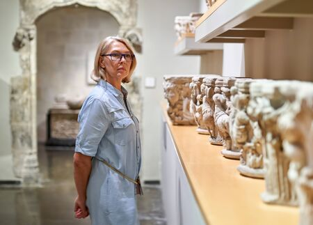 woman visitor in historical museum looking at art object