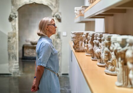 woman visitor in historical museum looking at art object Stock Photo