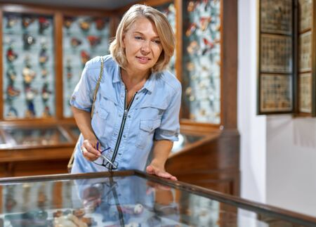 woman in museum looking at art object
