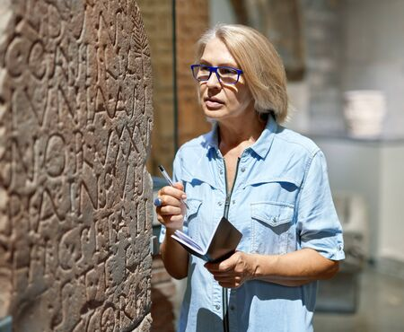 woman visitor looking at exhibition in museum of ancient sculpture