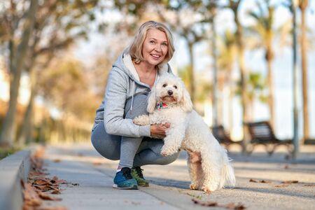 ältere frau, die mit einem hund im freien spazieren geht