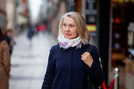 Happy pensioner woman walks on streets of a tourist city.