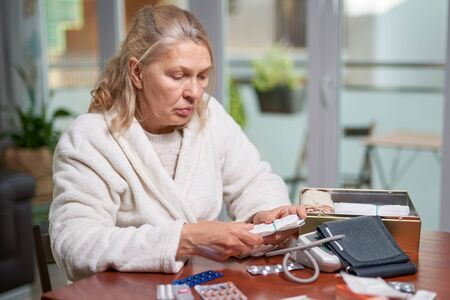 Portrait of troubled ill mature woman sitting at home and reading discription of medication in her hand
