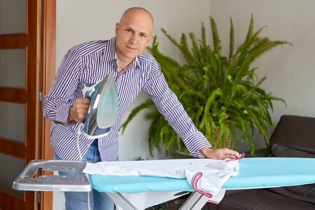 housework and household concept - man ironing shirt on iron board at home