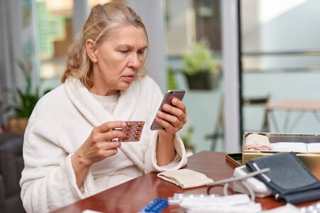 Portrait of troubled ill mature woman sitting at home and holding a phone and tablets Archivio Fotografico