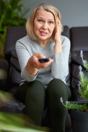 Adult woman at home sitting on the couch and watching tv, she is holding a remote control
