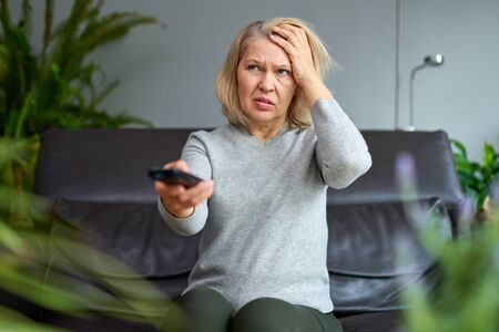 Adult woman watching television at home