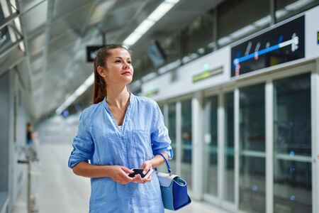 young woman with handbag in subway station