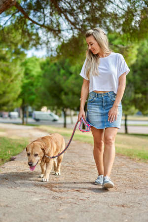 Woman walking the dog in the park.