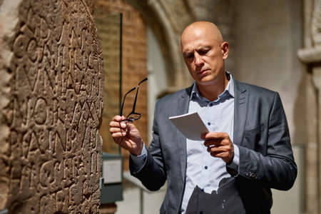 Man Holding a Guide Inside a Museum