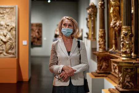 Woman exploring medieval expositions in museum wearing an antivirus mask Banque d'images