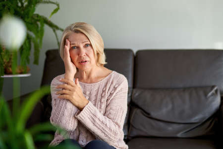 Woman suffering from a headache and stress holding her hands to her temples