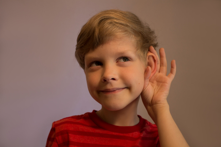 The boy listens very attentively. He listens very attentively. He pushes his ear and listens. His face is smiled. Stockfoto