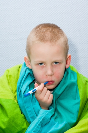 A sick little boy is measuring the temperature Stock Photo