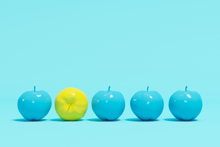 Outstanding yellow apple contrast blue appples on blue pastel background. minimal concept. Stock Photo