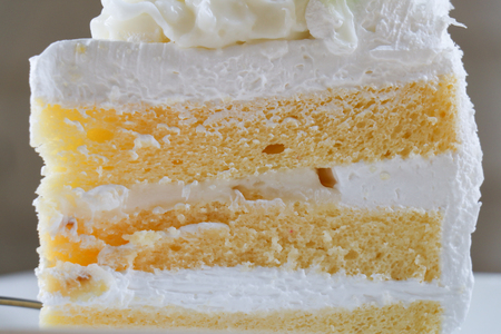 Closeup Piece of coconut cake on wooden table. selective focus. Stock Photo