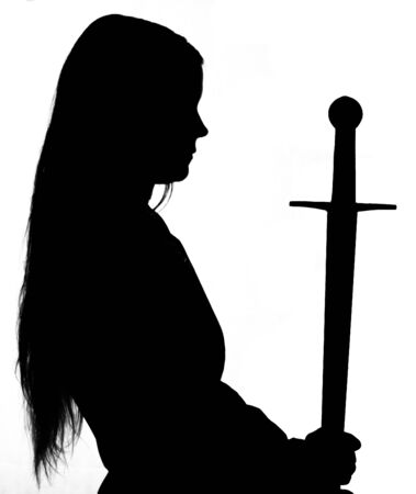 Silhouette of young long haired woman wearing a medieval costume presenting a sword at white studio background