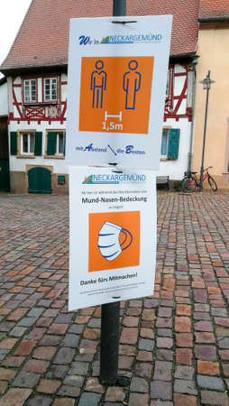 Neckargemuend, Germany: December 21, 2020: Signs about distance rules and mandatory masks to contain the Corona pandemic at the marketplace of Neckargemünd, a small town in southern Germany.