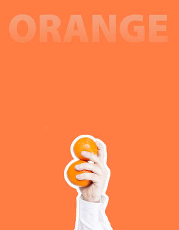 Hand holding two oranges and the word orange at a bright orange background, Collage in magazine style