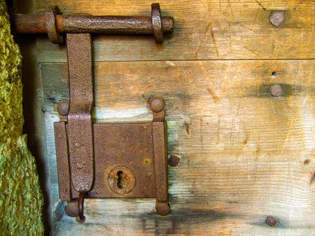 old rusted door fitting with big lock on wooden door