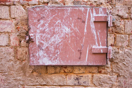 old metal flap on a brick wall during demolition of old house