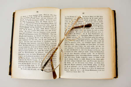 Reading glasses on an old book edition of Schiller`s works