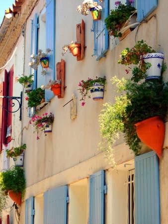 Mediterranean house facade with colorful flower hanging baskets Standard-Bild
