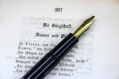Fountain pen on an old book with German text The Surety, poem by Friedrich Schiller in Fraktur script