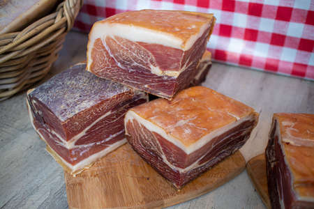 Large pieces of raw ham at a gourmet market with French products