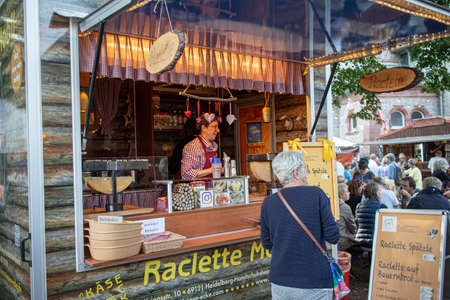 Neckargemuend, Germany: September 6, 2019: Market stall for Raclette and people at a gourmet market with French products