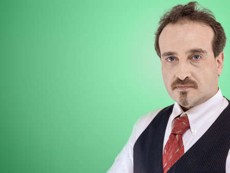 Man in white shirt, vest and tie business clothing looking at the camera front of a light green background. Free space at the left side of the image Standard-Bild